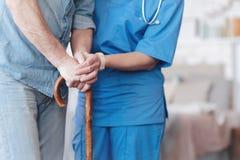 Zakończenie up żeńska pielęgniarka pomaga starszego pacjenta chodzić obrazy royalty free
