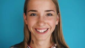 Zakończenie up blondynki dziewczyny śliczna twarz Dziewczyna jest przyglądająca w ono uśmiecha się i kamerze brunetek błękitny bo zbiory wideo