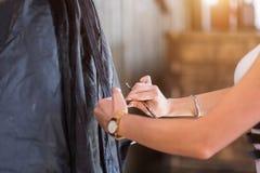Zakończenie up fryzjera mienia grępla i nożyce i robi ostrzyżenie kobiety klienta Zdjęcia Stock
