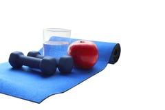 Zakończenie up jabłka dwa nieskazitelni czerwoni dumbbells i szkło woda, błękitny sportowy mały Zdjęcie Stock
