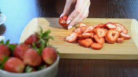 Zakończenie up kobiet ręki ciie truskawki na ciapanie desce i pokrajać zbiory wideo