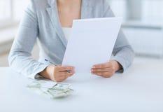 Zakończenie up kobiet ręki z pieniądze i podatku raportem Obrazy Royalty Free