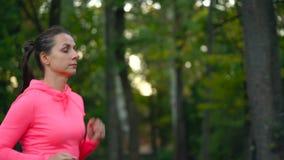 Zakończenie up kobieta bieg przez jesień parka przy zmierzchem swobodny ruch zdjęcie wideo