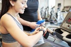 Zakończenie up kobieta ustawia tętno zegarek przy gym zdjęcia stock
