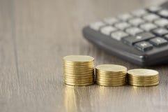 Zakończenie up kroka złociste monety plama kalkulatora drewna tło Zdjęcie Stock