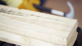Zakończenie up mężczyzna młotkuje gwóźdź drewniana deska zbiory