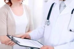 Zakończenie up męska lekarka trzyma podaniową formę podczas gdy konsultujący pacjenta Obraz Royalty Free