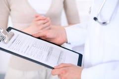 Zakończenie up męska lekarka trzyma podaniową formę podczas gdy konsultujący pacjenta Zdjęcia Stock