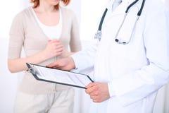 Zakończenie up męska lekarka trzyma podaniową formę podczas gdy konsultujący pacjenta Fotografia Stock