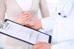 Zakończenie up męska lekarka trzyma podaniową formę podczas gdy konsultujący pacjenta Obraz Stock