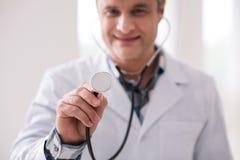 Zakończenie up męska ręka pokazuje szczegół od stetoskopu który Obrazy Stock