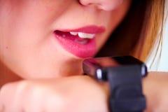 Zakończenie up młoda kobieta jest ubranym w jej nadgarstku mądrze zegarek z głos kontrola w słonecznego dnia tle, zdjęcia stock