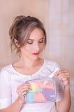 Zakończenie up młoda piękna uśmiechnięta kobieta trzyma miesiączka bawełnianego tampon w jej ręce i kolorowej kiesie w ona obraz stock