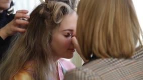 Zakończenie up młodej dziewczyny ` s makijażu proces przy piękno sklepem Młody visagiste stosuje eyeshadow na wzorcowej ` s twarz zbiory wideo
