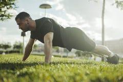 Zakończenie up młody atrakcyjny mężczyzna ćwiczy deskę outdoors Boczny widok obrazy stock