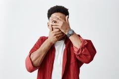 Zakończenie up młody ciemnoskóry mężczyzna z afro fryzurą w białej koszula pod czerwoną koszulową odzieży twarzą z rękami obraz stock