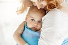 Zakończenie up małe dziecko patrzeje na boku w uroczych macierzystych rękach z dużymi popielatymi oczami Ona przytulenia uczucie  Zdjęcie Royalty Free