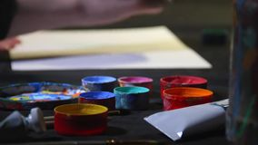 Zakończenie up malarza artysty ręka z szczotkarskim rysunkiem na białym prześcieradle i korek z farbą na papier i słoje zbiory