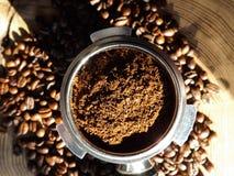 Zakończenie up metalu portafilter wypełniający z kawy wokoło prochowymi i kawowymi fasolami na drewnianym stole zdjęcia royalty free