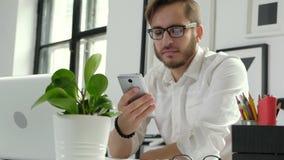 Zakończenie up modniś patrzeje jego smartphone ekran i trzyma pióro w jego ręce 20s 4k z długą brodą zbiory wideo