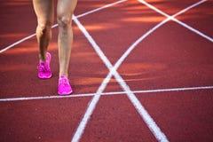 Zakończenie up na pięknych żeńskich nogach z różowymi butami na bieg śladzie Zdjęcia Stock
