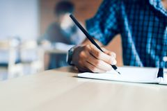 Zakończenie up nastolatek ręki studencki writing na papierowym egzaminie z p fotografia royalty free