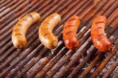 Zakończenie up opieczenie kiełbasy na grilla grillu BBQ w ogródzie Bawarskie kiełbasy obraz stock