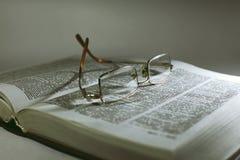 Zakończenie up otwierał książkową stronę i czytelniczych eyeglasses fotografia stock