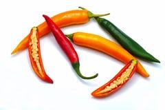 Zakończenie up pokrajać czerwień zielonego i pomarańczowego chili pieprzu biel fotografia stock