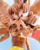Zakończenie up przyjaciele w okręgu na lato plaży Zdjęcia Stock