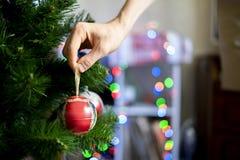 Zakończenie up ręka dekoruje chrismas drzewnych z piękną czerwoną piłki zabawką f obrazy stock