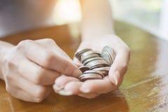 Zakończenie up ręka kobieta chwyta monety stos moneta dla ratować i Obrazy Royalty Free