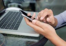 Zakończenie up ręka używać telefon na praca stole fotografia stock