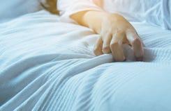 Zakończenie up ręki kobiety znaka orgazm, palcowego żeńskiego ciągnięcia biały bedsheet, pojęcie plciowi powiązania obrazy stock