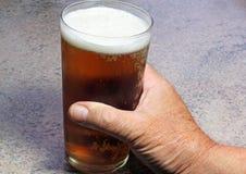 Zakończenie up ręki mienia napój w pół kwarty szkle Fotografia Stock