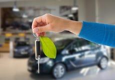Zakończenie up ręki mienia samochodu klucz z zielonym liściem Fotografia Royalty Free
