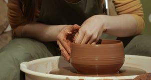 Zakończenie up ręki pracuje glinę na garncarki ` s kole, zakończenie widok zbiory