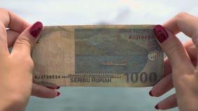 Zakończenie up 1000 rupii rachunek w rękach w to samo miejsce na ternate wyspie zdjęcie wideo