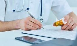 Zakończenie up samiec lekarki ` s ręki writing recepty kapsuły i papier obrazy stock