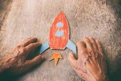Zakończenie up starszy mężczyzna trzyma papierową rakietę na drewnianym stole Pojęcie główkowanie o sen, smuceniu i lonie dzieciń Obraz Royalty Free