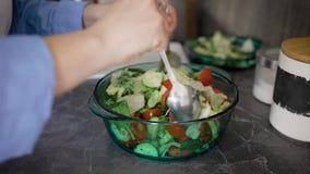 Zakończenie up strzelał kobieta miesza zielonych świeżych warzywa w szklanym pucharze na kuchennym kontuarze zbiory