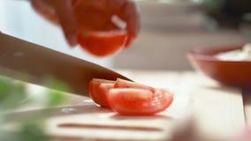 Zakończenie up strzelał ręki kobiety używa kuchennego noża obruszenia rżniętego świeżego pomidoru na drewnianym tnącej deski narz zbiory