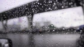 Zakończenie up strzelał raindrop na samochodowym nadokiennym szkle i rozmytego ruch drogowego na nastroju dżdżystym chmurzącym ci zbiory