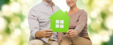 Zakończenie up szczęśliwa starsza para z zielonym domem Obrazy Stock