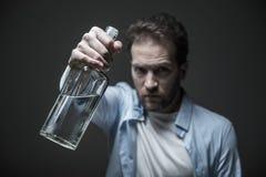 Zakończenie up szklana butelka jest w męskich rękach Zdjęcie Stock