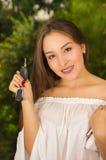 Zakończenie up uśmiechnięta piękna młoda kobieta trzyma ona wewnątrz klucze w jeden ręce kiesa w jej innej ręce i pastylka i Fotografia Royalty Free