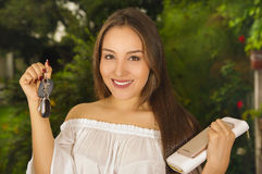 Zakończenie up uśmiechnięta piękna młoda kobieta trzyma ona wewnątrz klucze w jeden ręce kiesa w jej innej ręce i pastylka i Zdjęcie Royalty Free