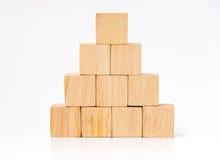 Zakończenie up układa w ostrosłupa kształcie przy drewnianym sześcianem, biznesowy concpt Obrazy Royalty Free