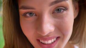 Zakończenie urocza blond dziewczyna patrzeje kamerę prostą i ono uśmiecha się plenerowy