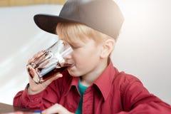 Zakończenie urocza małe dziecko chłopiec pije sok w lecie w eleganckiej nakrętce podczas gdy siedzący w restauraci Chłopiec z szk Zdjęcia Royalty Free